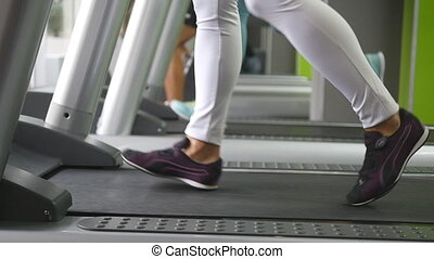 Female legs walking and running on treadmill in gym. Young woman exercising during cardio workout. Feet of girls in sport shoes training indoor at sport club. Slow motion Close up