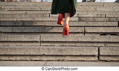 Female legs walking upstairs on stone staircase