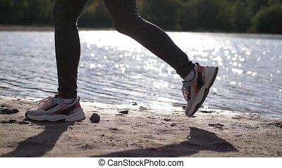 Female legs wear sneakers close up running along coast. slow...