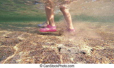 Female legs with pink manicured toes walking underwater. Point of view of woman walking in sea water at sandy beach. Underwater footsteps of a girl in the shallow water on a sandy seabed