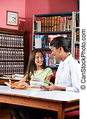 Female librarian and schoolgirl looking at each other while sitting with books at table in library