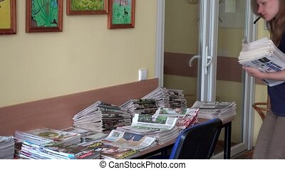 Female librarian girl sorting daily newspapers on table in library room.