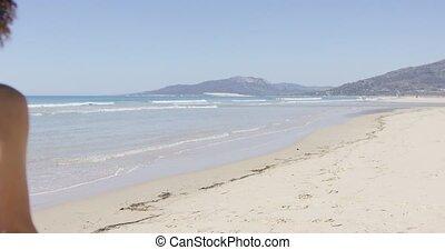 Female lifeguard wearing red swimsuit goes along beach, back view. Tarifa beach. Provincia Cadiz. Spain.