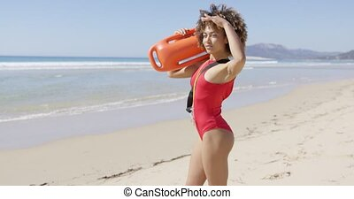 Female lifeguard looking into the distance placing her hand to forehead on Tarifa beach. Provincia Cadiz. Spain.