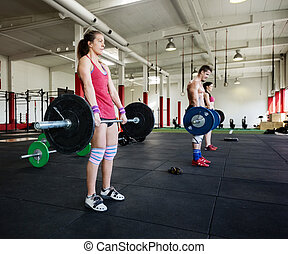 Female Lifting Barbells With Friends In Gym