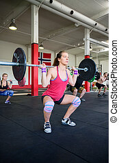 Female Lifting Heavy Barbell In Gym