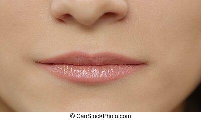 Female lips. Girl showing braces on teeth. White. Closeup -...