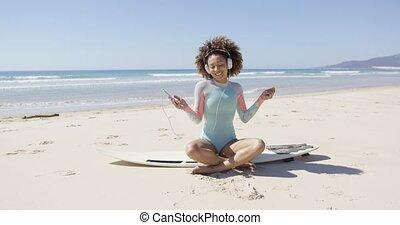 Female listening music on sea background