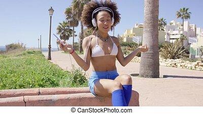 Female listening music with headphones - Smiling female...
