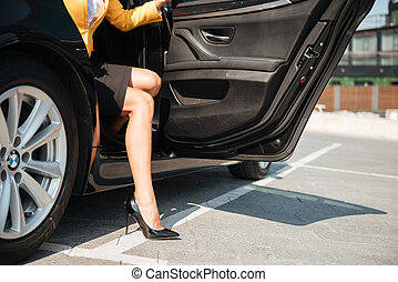 Female long legs getting out of her car - Close up portrait...