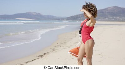 Female looking into distance on beach - Female looking into...