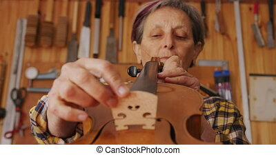 Female luthier at work in her workshop - Front view close up...