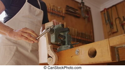 Female luthier at work in her workshop - Low angle mid ...
