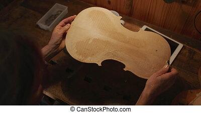 Female luthier at work in her workshop - Over the shoulder ...