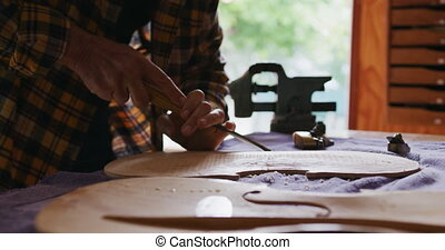 Female luthier at work in her workshop - Side view mid ...