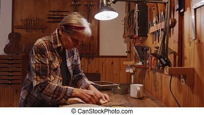 Female luthier at work in her workshop - Side view of a ...