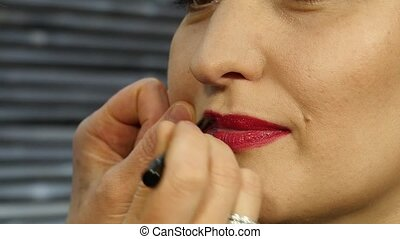 Female make-up artist apply pink lipstick with brush on a client lips