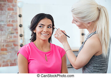 Female makeup artist applying professional brush for eyes of  woman