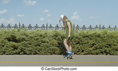 Female making moonwalk on roller blades in park - Carefree...