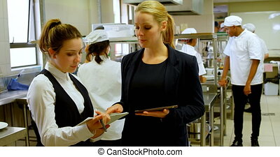 Female manager and female chefs discussing over clipboard 4k