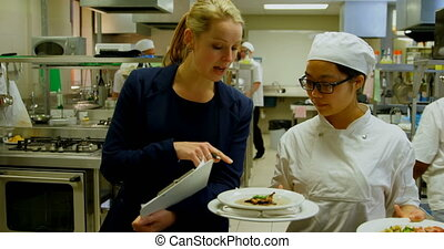 Female manager and female chefs interacting with each other in kitchen 4k