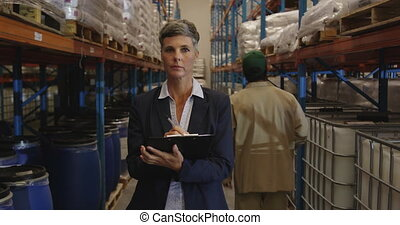 Female manager checks stock in a warehouse 4k