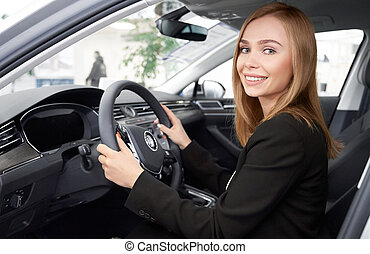 Female manager of dealership sitting in car driver's seat.