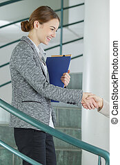female manager shaking hands with customer