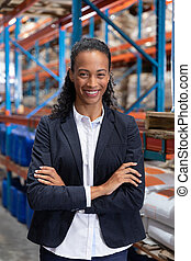 Close-up of female manager standing with arms crossed in warehouse. This is a freight transportation and distribution warehouse. Industrial and industrial workers concept