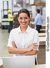 Female manager with arms crossed in warehouse
