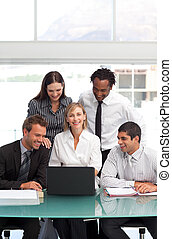 Female manager working with her team with a laptop