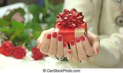 Female manicured hands with gift box. Handmade gift box with...