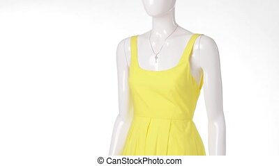 Female mannequin in yellow dress.