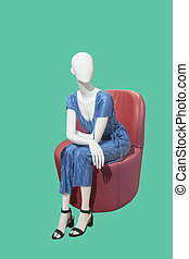 Female mannequin sitting on a chair.