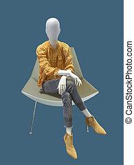 Female mannequin sitting on armchair.
