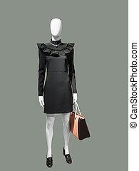 Female mannequin wearing black dress