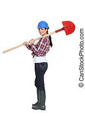 Female manual worker carrying shovel