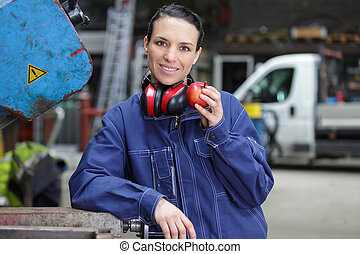 female manual worker eating apple for lunch