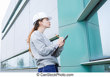 female manufacturing labourer outdoors holding clipboard