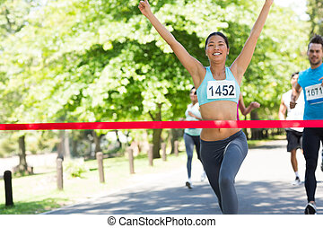 Female marathon winner with arms raised crossing finish line