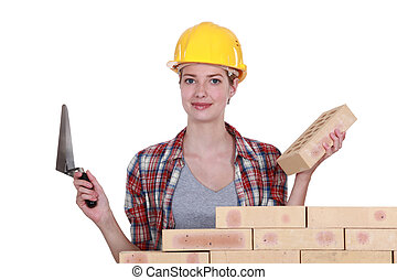 Female mason stood by wall with trowel