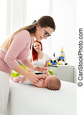 Female massage therapist or a doctor examining newborn baby boy with the mother watching in the background. Baby massage concept.