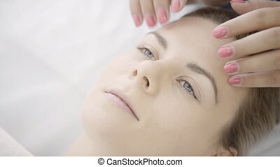 Female masseur makes facial massage of lying woman in clinic indoor.
