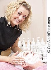 Female masseuse giving client facial