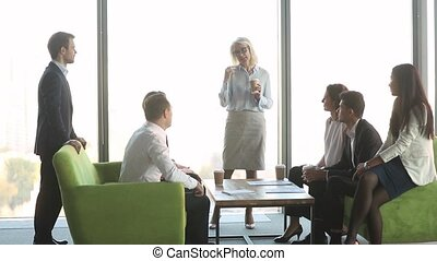 Female mature leader talking to workers clients at coffee...