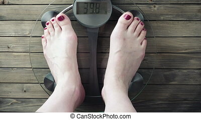 Female measuring weight on health scale