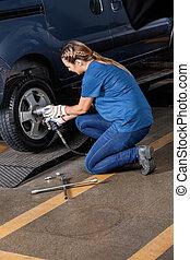 Female Mechanic Adjusting Car Tire