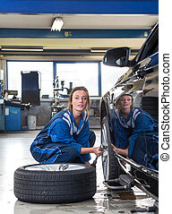 Female mechanic changing a tyre