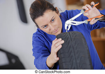 female mechanic changing car tire