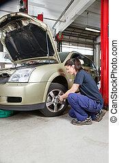 Female mechanic changing wheel